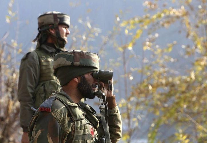 Dos soldados indios permanecen en guardia durante un combate con presuntos insurgentes en Gingal, India. (EFE)