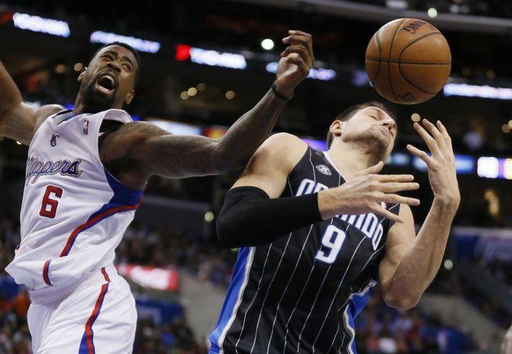 Nikola Vecevic (d), de Orlando Magic, disputa un rebote con DeAndre Jordan, de Clippers, en la primera mitad del partido de este lunes por la noche en Los Angeles. (Agencias)