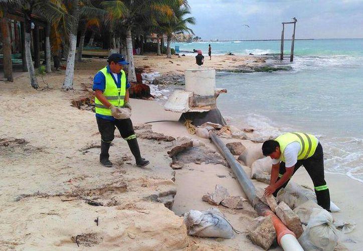 Trabajadores de Aguakan colocaron costales de arena y piedras para disminuir las afectaciones en la línea. (Foto: Daniel Pacheco/SIPSE)