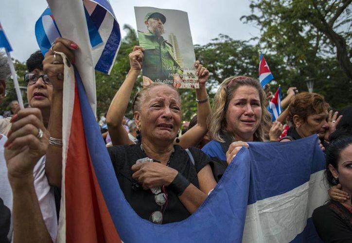 Mujeres lloran mientras la procesión de las cenizas del líder cubano Fidel Castro sale de la ciudad de Santa Clara, Cuba. (AP/Desmond Boylan)