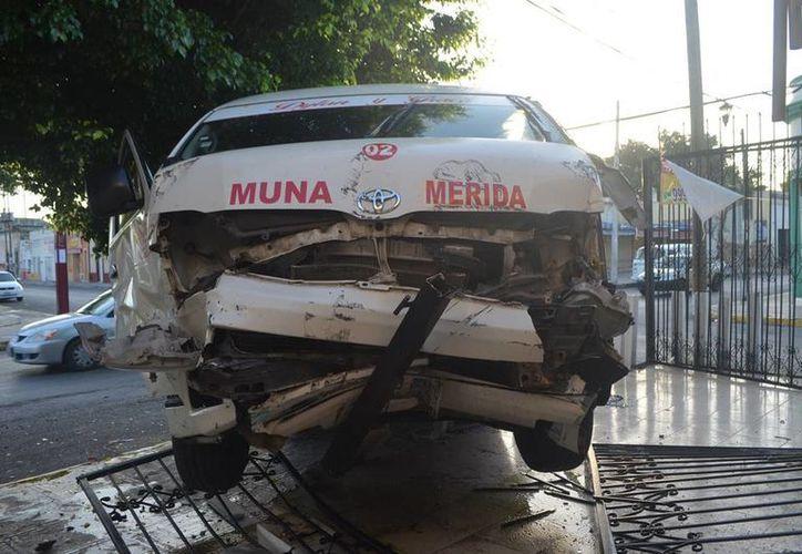 Un taxi colectivo se pasó el alto y fue chocado por otro vehículo de transporte público: un taxímetro. La Urvan acabó en la terraza de una domicilio, en San Sebastián. (Carlos Navarrete/SIPSE)