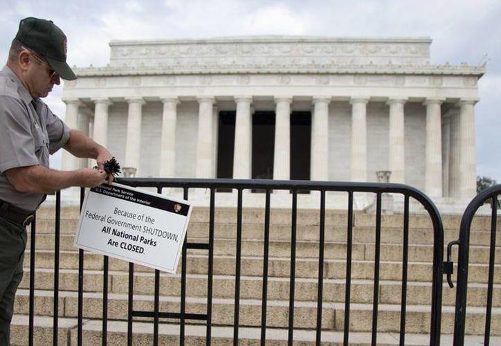 Un policía coloca un letrero en una barricada que impide el acceso al Monumento a Lincoln en Washington. (Agencias)