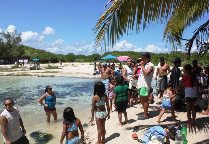 Con un megáfono en mano, Juan Carlos Jiménez, invita a la gente a participar en la campaña de limpieza y cultural en Punta Esmeralda.  (Daniel Pacheco/SIPSE)