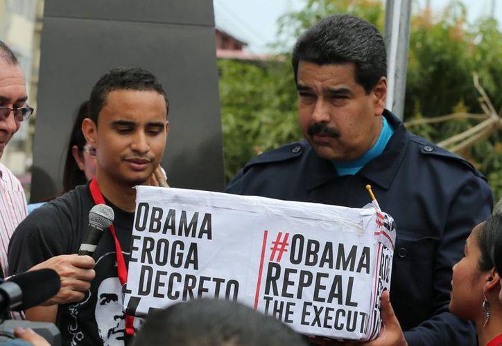 El presidente venezolano Nicolás Maduro sostiene una caja cubierta por 'hashtags' con firmas de partidarios que piden a Estados Unidos acabar con las sanciones contra Venezuela. Maduro se convirtió en la figura pública con más retweets del mundo. (Foto AP/Ramón Espinosa, Archivo)