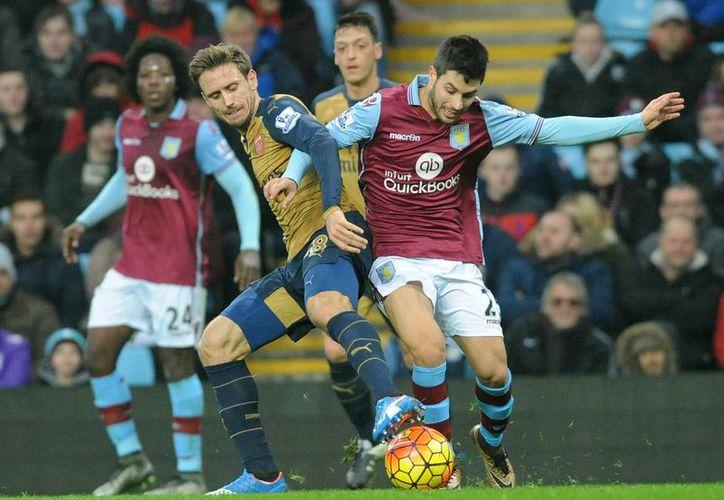 Nacho Monreal (i), del Arsenal, y Carles Gil, de Aston Villa, luchan por el esférico en partido de Liga Premier ganado por los primeros, que subieron como líderes y dejaron a su rival en el fondo de la tabla. (AP)