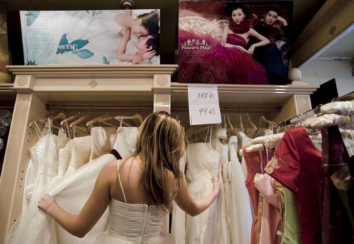 Una mujer observa algunos modelos de trajes de novia, en Madrid, España. (EFE/Archivo)