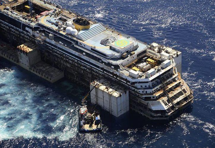 El barco Costa Concordia, que naufragó en 2012 en la isla de Giglio, es arrastrado por varios botes remolcadores hacia Génova, donde será destruído. (Agencias)