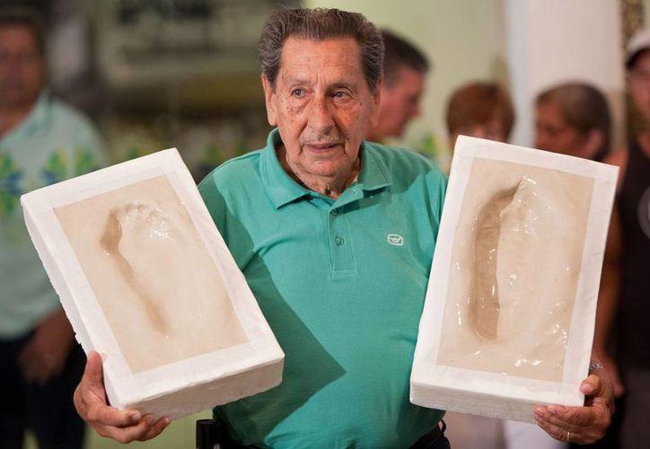 Ghiggia, quien falleció este jueves a los 88 años, exactamente 65 años después de meter el gol con el que Uruguay le dio la vuelta a Brasil en la final de Maracaná, muestra, en foto de 2009, los moldes con las huellas de sus pies, que fueron colocados en dicho estadio. (Foto: AP)