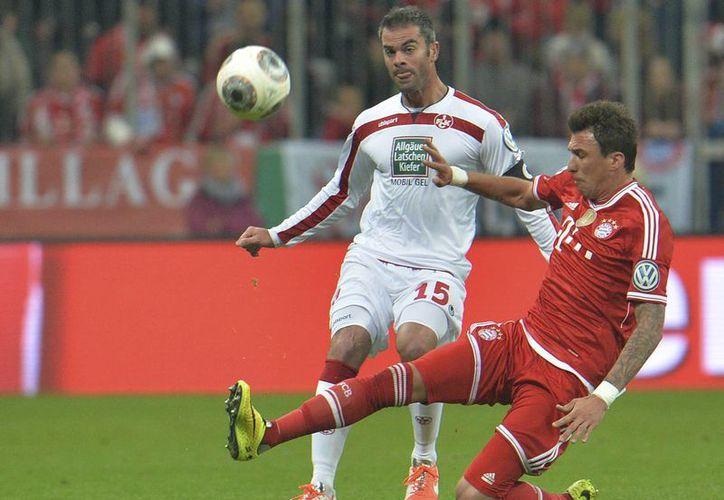 Mandzukic (d), uno de los goleadores del Bayern, disputa el balón con Marc Torrejon, del Kaiserslautern. (Foto: AP)