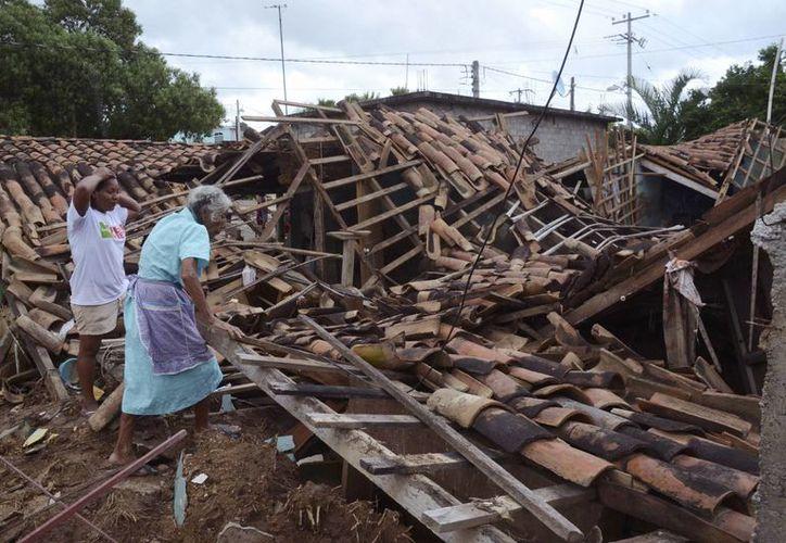Mujeres tratan de recuperar lo poco que les queda en la comunidad de Salsipuedes, México. (Agencias)