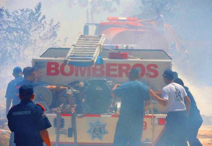 Los bomberos aseguran que el incendio cercano a Villas del Sol fue reactivado a propósito. (Daniel Pacheco/SIPSE)