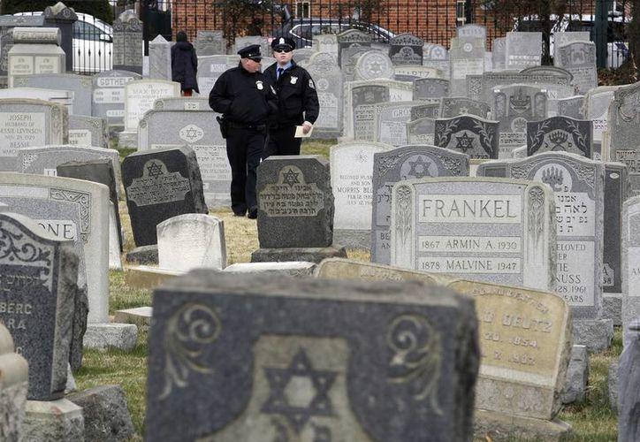 Esta mañana aparecieron lápidas judías derribadas y manchadas en el Cementerio Waad Hakolel en Rochester. Imagen de contexto de dos policías de Filadelfia que caminan en medio de más de 100 lápidas vandalizadas en el Cementerio de Mount Carmel. (Foto AP / Jacqueline Larma)