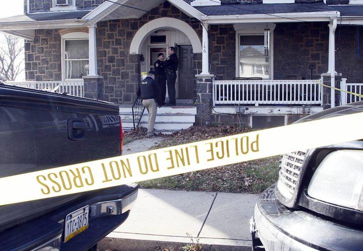 Unos policías permanecen en la entrada de una residencia donde presuntamente un hombre armado asesinó al residente de la propiedad. (Archivo/EFE)
