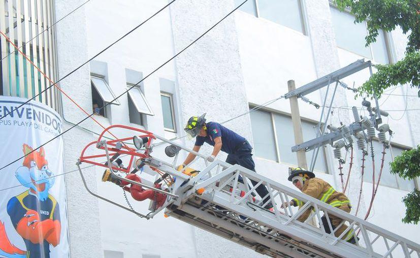 Bomberos utilizaron una escalera telescópica para bajar al afectado del techo del edificio de cinco niveles de la UNID. (Redacción/SIPSE)