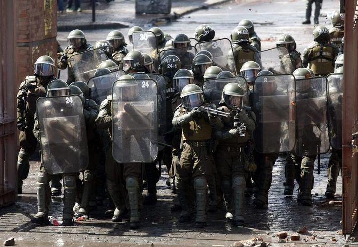 Policías antidisturbios se posicionan para disolver a los manifestantes el pasado 7 de septiembre de 2014, durante una marcha por las calles céntricas de la capital chilena. (Archivo/EFE)