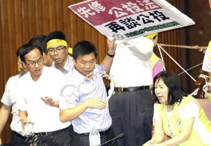 Varios legisladores se lanzan agua entre ellos, en el Parlamento taiwanés en Taipei, hoy, viernes 2 de agosto de 2013. (EFE)