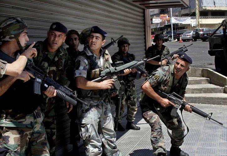 Soldados del ejército libanés toman posiciones durante los combates con los seguidores del clérigo radical suní Sheik Ahmad al-Assir en Saida, un puerto del sur libanés. (Agencias)