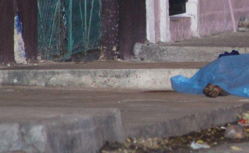 El cadáver de un hombre quedó tirado en la calle, luego de que vándalos lo atacaran y le quitaran la vida. (Martín González/SIPSE)