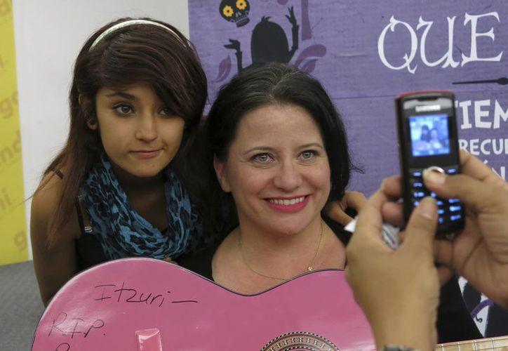 Hurley con su fan Itzuri Morales durante una sesión de autógrafos. (Agencias)