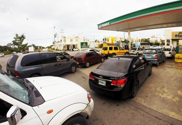 Anuncian los precios máximos por litro de gasolina en la frontera de México-EU. Imagen de contexto de la fila de un grupo de autos en una gasolinera. (Archivo/Notimex)