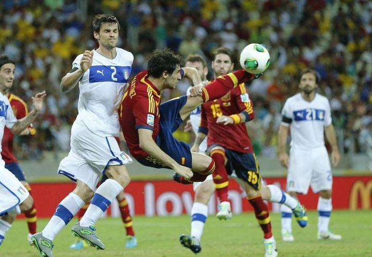 Javier Martinez (ESP) pelea el balón al italiano Christian Maggio. (Agencias)