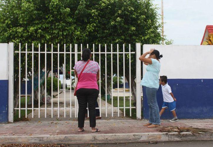 Padres de familia se encontraron con un cartel al momento de dejar a sus hijos en las escuelas. (Harold Alcocer/SIPSE)