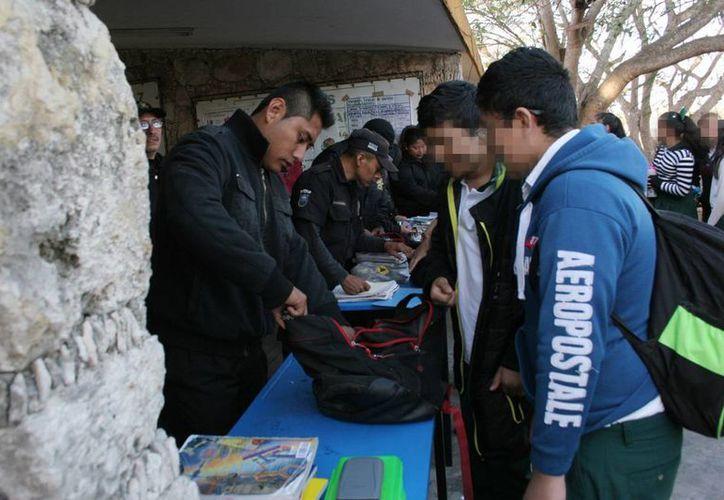 Elementos de la Policía municipal,  padres de familia y directivos de la Secundaria Técnica 7 se encargaron de revisar las mochilas de los estudiantes, antes de entrar a clases. (Milenio Novedades)