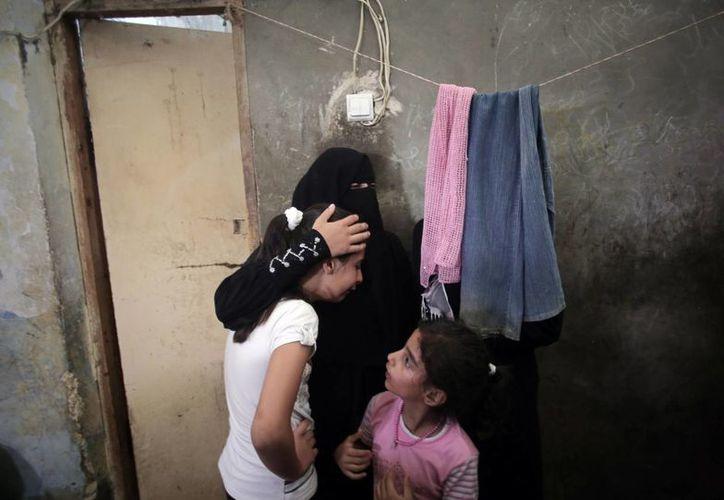 Pariestes de la familia palestina que fue asesinada durante un ataque en la mañana, lloran durante su funeral en el  campamento de refugiados de Khan Younis, sur de la Franja de Gaza. (Agencias)