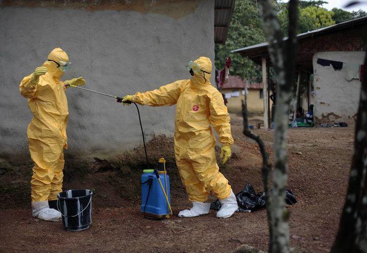 Konah Deno (d) limpia a su compañero Gordon Kamara, luego de que ambos trataran a seis personas sospechosas de portar el virus del ébola en la Reserva Freeman, en Liberia. (Foto de contexto de AP)
