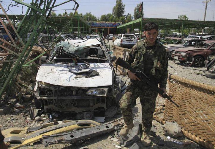 Un oficial afgano inspecciona la zona tras un atentado suicida contra un convoy de la OTAN en Jalalabad, Afganistán. (EFE)