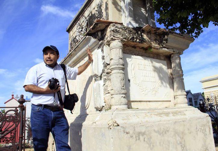 Luis Ojeda, presidente de la Ayerac, junto a una tumba deteriorada. (Theani Ruz/SIPSE)