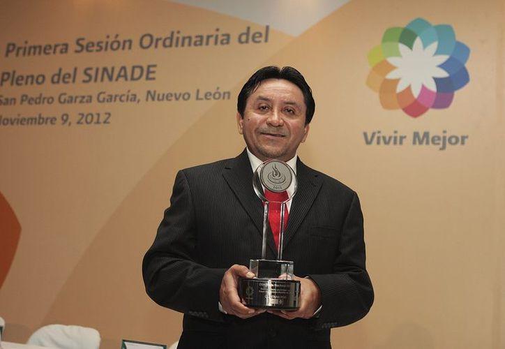En representación del gobernador Roberto Borge, el presidente de la Cojudeq, Normando Medina Castro, recibe el galardón. (Cortesía/SIPSE)