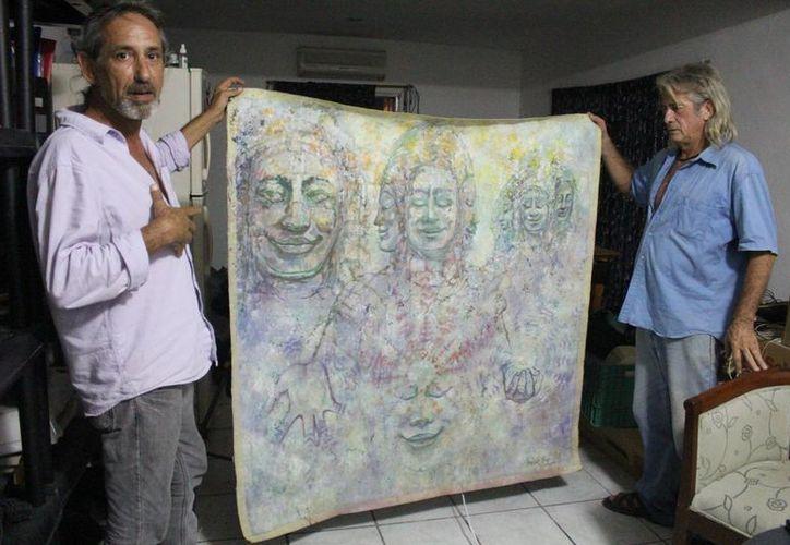 Andrés Morales y Raymundo Tineo sostienen un lienzo expuesto en alguna de las muestras que organizó en su momento el colectivo artístico Hecho en Playa, del cual fueron fundadores. (Luis Ballesteros/SIPSE)