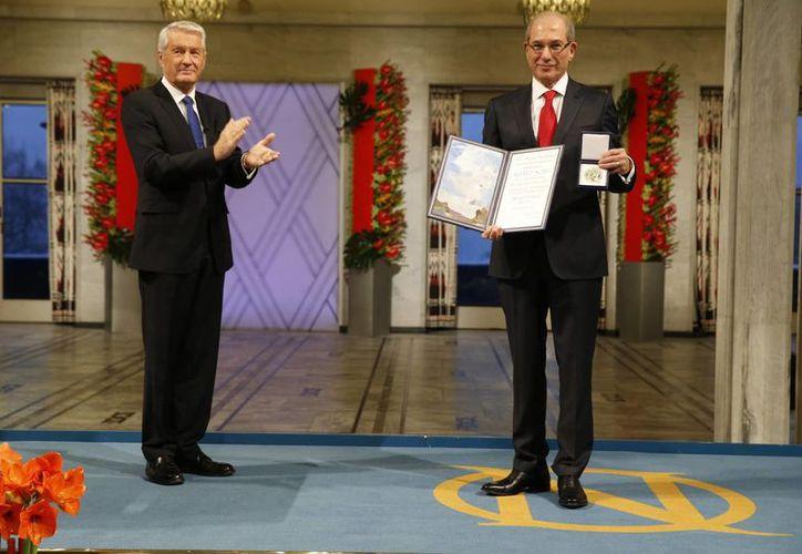 Ahmet Uzumcu (d), Director General de la Organización para la Prohibición de las Armas Químicas recibe el Premio Nobel de la Paz del presidente del Comité Noruego del Nobel, Thorbjorn Jagland. (Agencias)