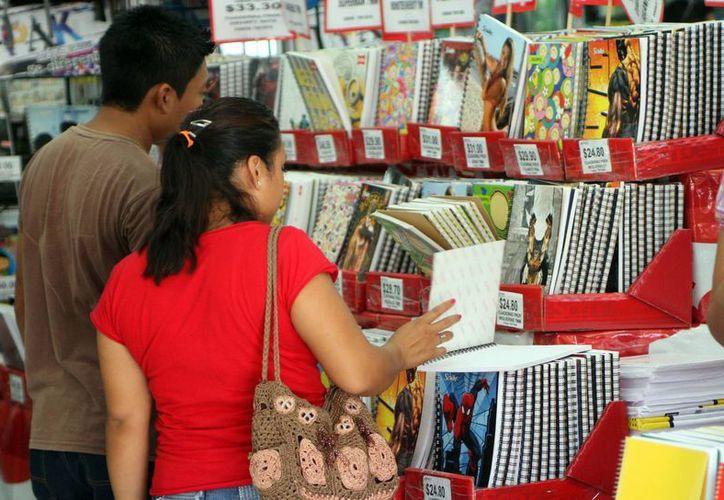 La Profeco alerta sobre la venta de artículos que no cumplen las normas. Imagen de una pareja que realiza la compra de útiles escolares. (Milenio Novedades)