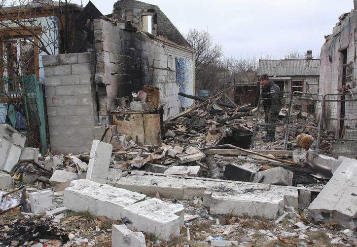 Un rebelde prorruso camina entre edificios derruidos en una calle en Donetsk, Ucrania. (EFE)