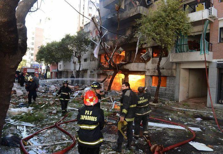 Bomberos a las afueras del edificio de diez pisos en el que se registró una fuerte explosión. (EFE)