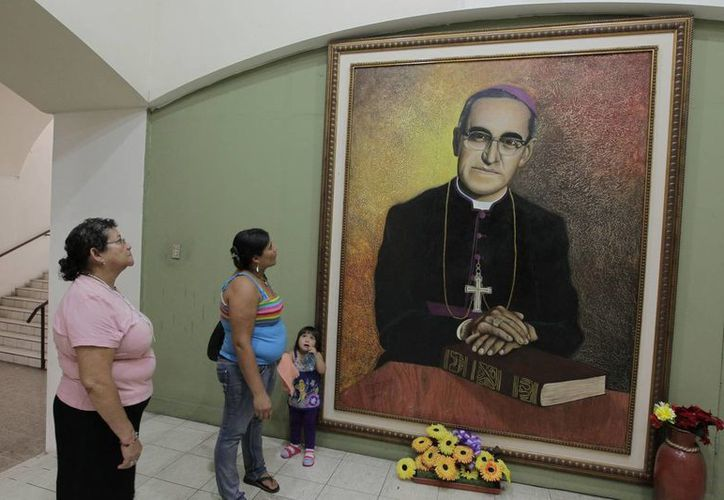 Salvadoreñas observan una pintura del arzobispo de San Salvador Óscar Arnulfo Romero, asesinado por un francotirador el 24 de marzo de 1980. (EFE)