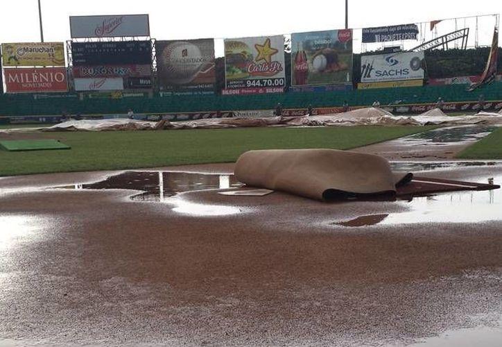 """El diamante del parque """"Kukulcán"""" quedó anegado este jueves por la tarde y obligó a la cancelación del partido entre Leones y Olmecas. (Milenio Novedades)"""
