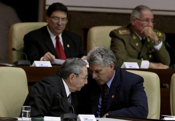 El nuevo vicepresidente de Cuba, Miguel Díaz Canel, derecha al frente, y el presidente cubano Raúl Castro conversan en la Asamblea Nacional en La Habana. (Agencias)