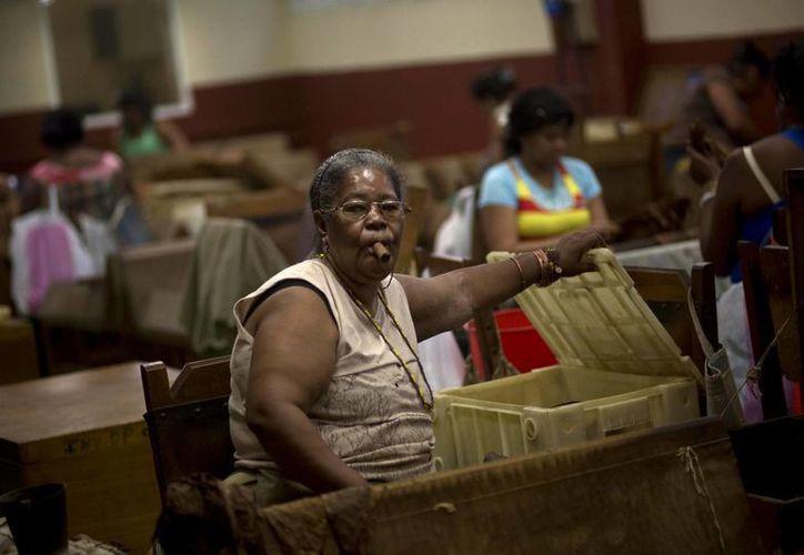 Un mujer fuma un puro mientras selecciona tabaco en la fábrica de habanos H. Upmann en la Habana, Cuba. (Agencias)