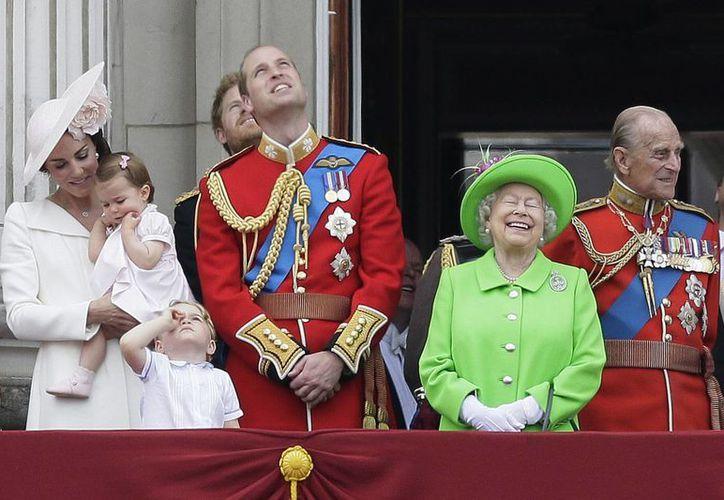 La reina Isabel II sonríe con el Príncipe Felipe (der), el príncipe Guillermo (c), su hijo el príncipe George (delante), la duquesa de Cambridge Kate y la pequeña princesa Charlotte en el balcón durante el desfile en el Buckingham, Londres. (Agencias)