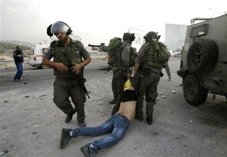 Militares israelíes arrestan a un palestino durante una protesta en la Franja de Gaza, el domingo 18 de noviembre de 2012. (Agencias)