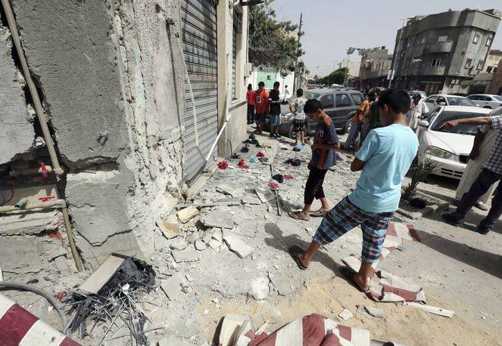 Varios niños observan los desperfectos causados tras un ataque en Trípoli. (Archivo/EFE)
