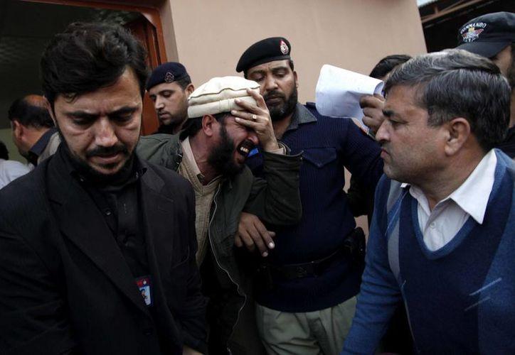 Familiares de las víctimas del atentado suicida que tuvo lugar en las oficinas de la Autoridad Nacional de Base de Datos y Registro lloran a la entrada de un hospital en Mardan, Pakistán. (EFE)