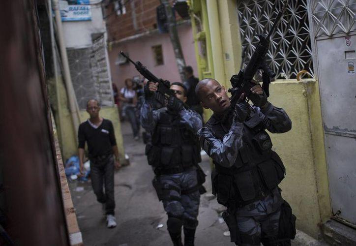 Policías militares patrullan el barrio de Roquette Pinto, en la favela de Mare, en Río de Janeiro. (Agencias)