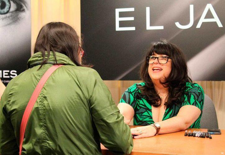 La autora británica E.L. James (de fente) lanzó, 'Grey', novela saga de la historia que la hiciera famosa '50 Sombras de Grey'. En la imagen, las escritora platica con una de sus fans, durante una firma de autógrafos. (EFE)