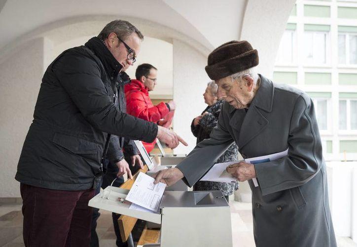 Los suizos votaron este domingo sobre medidas que endurezcan la ley contra extranjeros que cometan delitos, incluso menores. En la foto, un hombre deposita su voto en una oficina electoral en Appenzell, Suiza. (EFE)