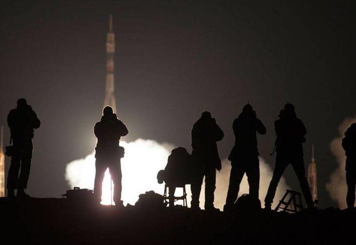 Periodistas gráficos toman fotos del despegue de la nave Soyuz que viaja a la Estación Espacial Internacional, en donde dos astronautas vivirán por lo menos un año. (AP)