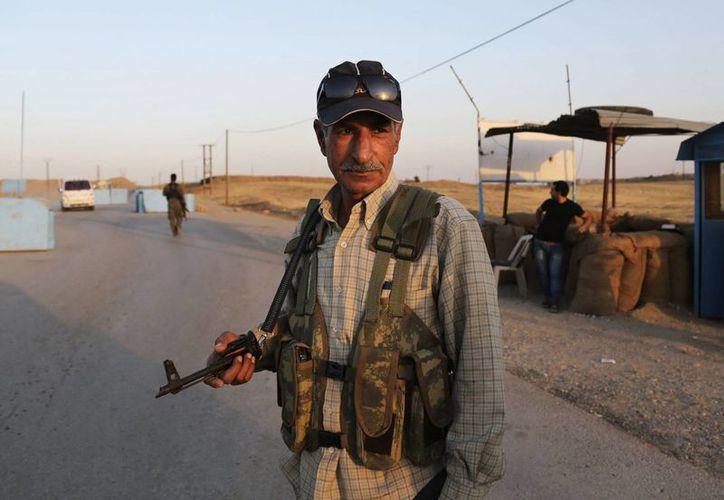 Combatientes sirios curdos montan guardia en un campo de refugiados en Derike, Siria. (Agencias)